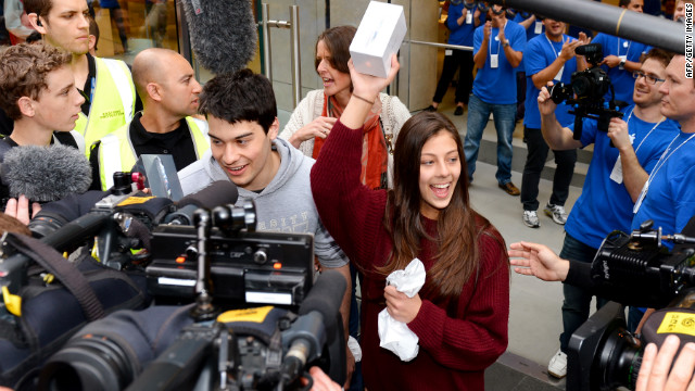 Tamsyn Vohradsky holds up her iPhone 5 after becoming the first buyer of Apple's new smartphone at a store in Sydney, Australia, on Friday, September 21.