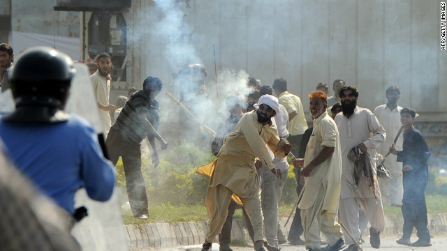 A demonstrator in Islamabad, Pakistan, throws a tear gas shell at riot police during a protest Friday against an anti-Islam film.