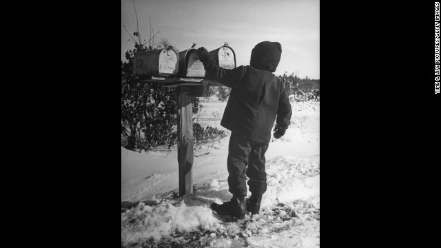 A Wisconsinite opens the family mailbox in 1946. See more photos of the classic Postal Service from Life.com.