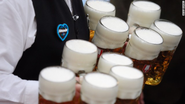 A waiter brings beer mugs to participants.