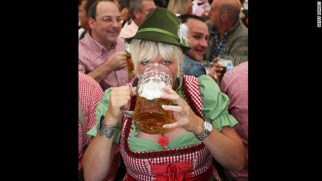 A woman wearing a traditional Bavarian Dirndl dress drinks beer.
