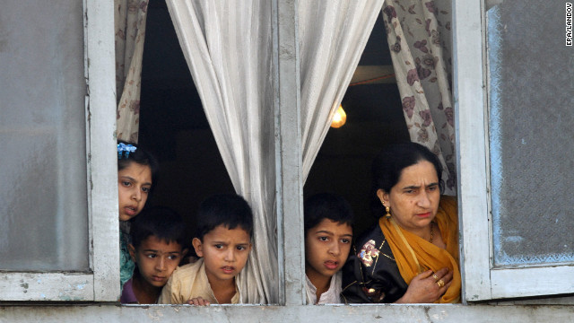 A family in Kashmir watches as students protest on Saturday.