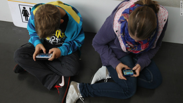 A boy and a girl play video games on their phones in September 2012 in Ruesselsheim, Germany.