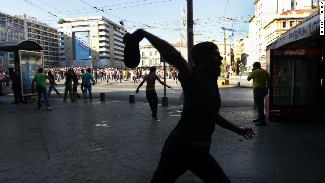 A Muslim protester throws a shoe at police during a rally in central Athens on Sunday.