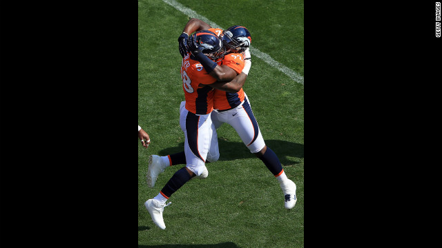 Elvis Dumervil of the Broncos, right, celebrates his safety with Von Miller on Sunday against the Texans.
