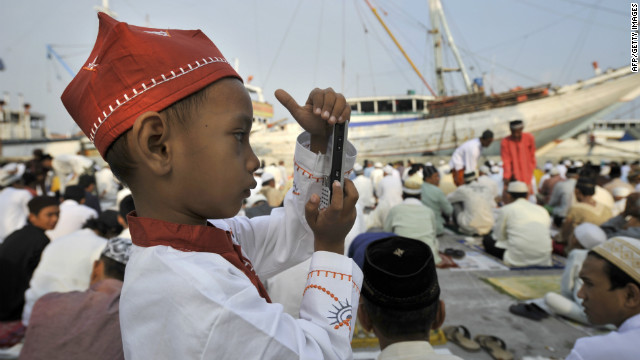 A young Indonesian boy takes a photo with a mobile phone following prayers at the old Jakarta port of Sunda Kelapa where he was celebrating the three-day Eid al-Fitr festival. 