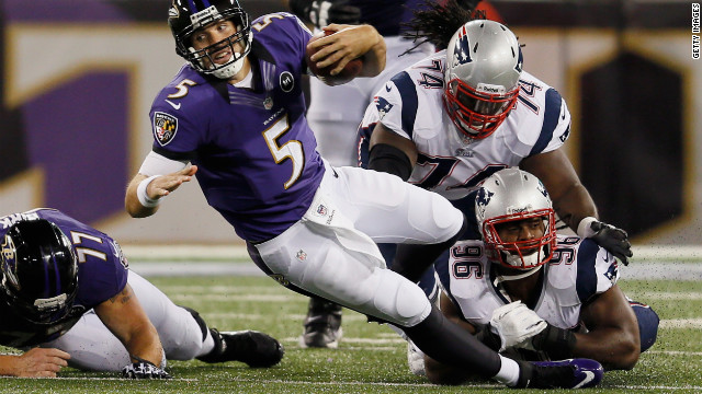 Quarterback Joe Flacco of the Ravens is brought down by No. 74 Kyle Love and No. 96 Jermaine Cunningham of the Patriots after scrambling for a first down on Sunday.