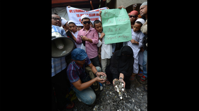 Philippine Muslims gather coins they collected from the provinces to be used to pay for filing a petition before the Philippine Supreme Court in Manila on Monday asking for local authorities to ban the controversial &quot;Innocence of Muslims&quot; film from being posted on the Internet. Hundreds of Muslim protesters in the Philippines called for a ban on the film before the U.S. Embassy.