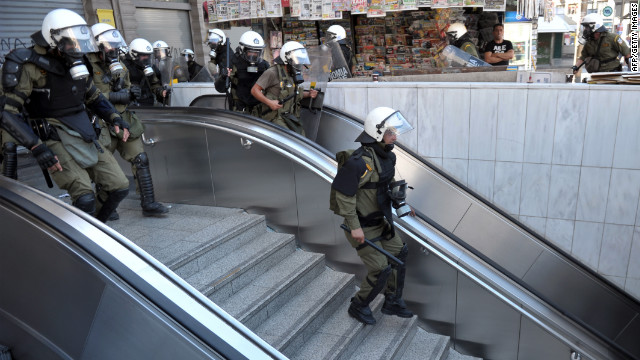 Police chase rioting youths at a subway entrance in the center of Athens Wednesday.