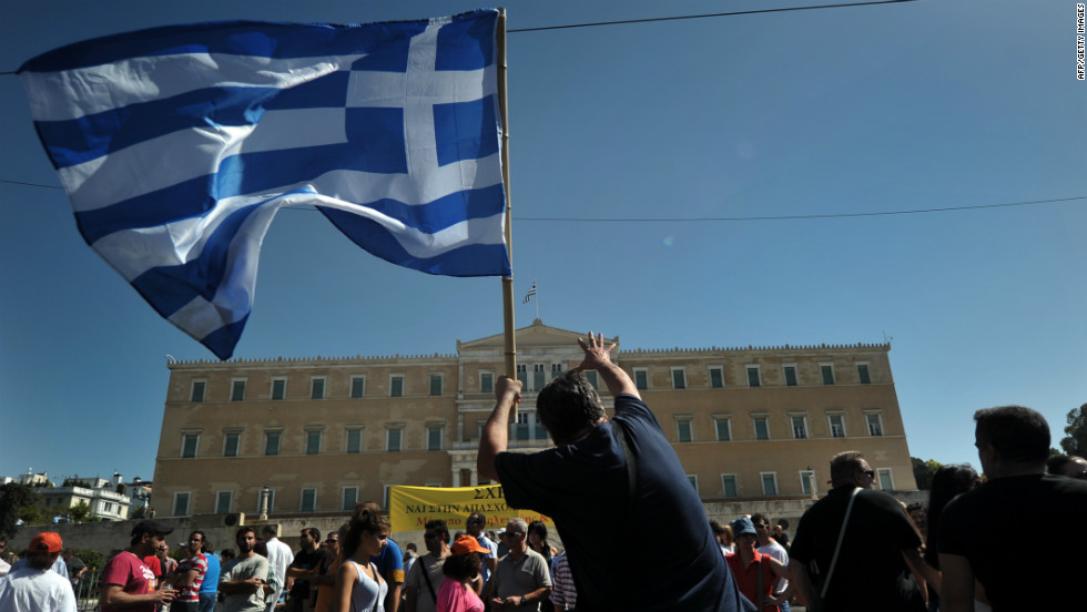 A protester holding a Greek flag gestures toward parliament in Athens on Wednesday, September 26. Greek trade unions called a 24-hour general strike to oppose new austerity measures. Police said some protesters threw Molotov cocktails in Syntagma Square, opposite the parliament building. Police responded with tear gas. <a href='http://www.cnn.com/2012/09/26/europe/gallery/spain-protest/index.html'>See anti-austerity protests in Spain</a>.