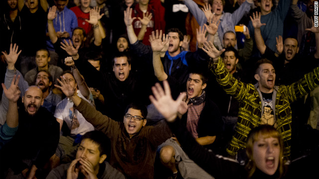 Demonstrators raise their hands during the protest against government spending cuts.