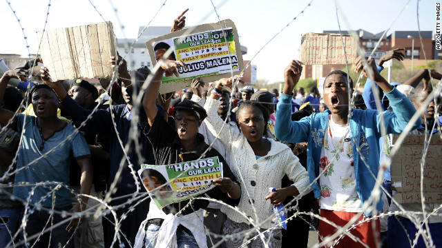 Demonstrators gather behind a razor wire outside the courthouse on September 26, singing songs in Malema's support. Some held an overnight vigil at a local hall amid heavy security presence that included riot police.<br/><br/>