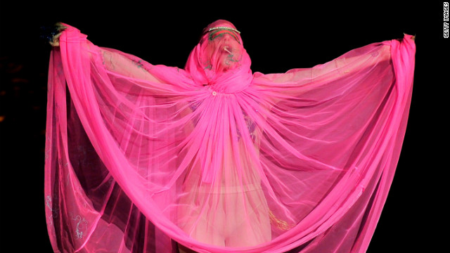 Lady Gaga drapes herself in pink on the catwalk at the Philip Treacy fashion show.