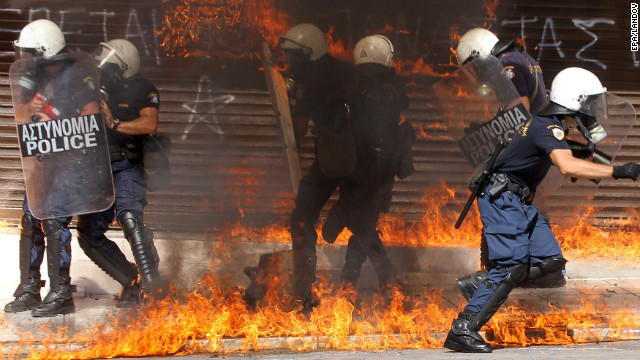 Riot police are surrounded by flames during violent clashes in Athens on Wednesday.
