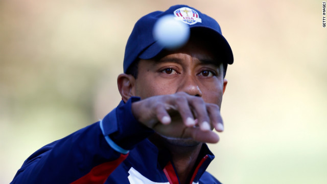 Team U.S.'s Tiger Woods reaches for a golf ball on the practice ground on Thursday.