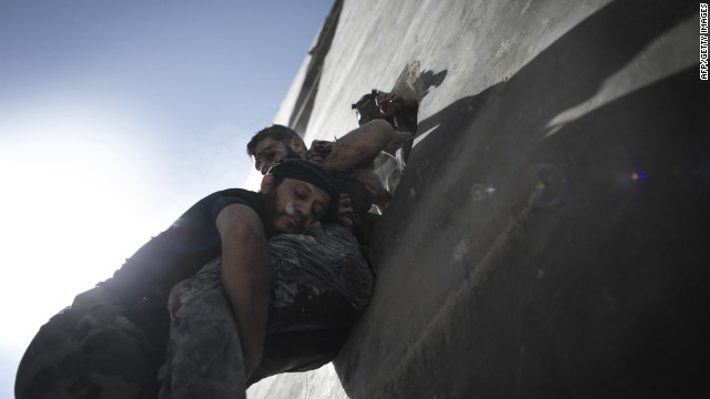 Men carry the covered body of a child killed in an attack by Syrian government forces in Aleppo on Friday, Spetember 28.