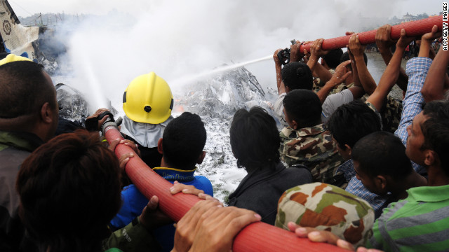 Nepalese firefighters and volunteers try to put out flames from the wreckage.