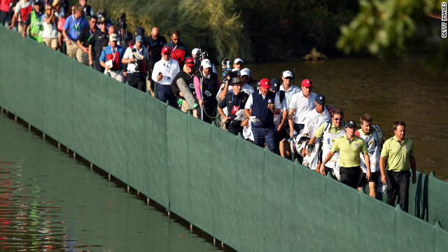 McIlroy and McDowell walk across a bridge ahead of the gallery on Friday.