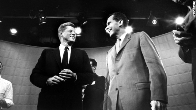 John F. Kennedy and Richard Nixon exchange smiles beneath glaring lights before their first TV debate in 1960. 