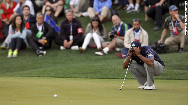 Tiger Woods of the United States scopes out a putt on the 17th hole during four-ball play Saturday.