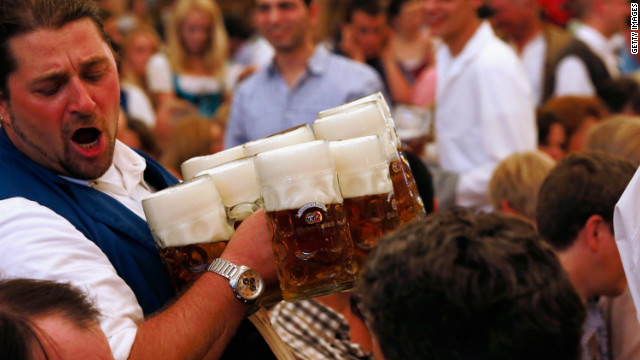 A waiter carries beer mugs through the Braeurosl beer tent during day seven of Oktoberfest 2012 on Friday, September 28, in Munich.
