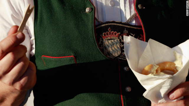 A man dressed in traditional Bavarian clothing eats fried calamari on Friday.