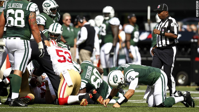 Quaterback Mark Sanchez of the New York Jets, right, gets back to his feet after a fumble against the San Francisco 49ers on Sunday at MetLife Stadium in East Rutherford, New Jersey.