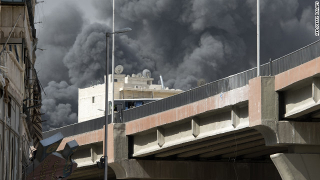 Smoke billows from a burning textile factory after Syrian regime forces shelled a nearby position held by rebels in the Aleppo neighbourhood of Arqub Sunday.