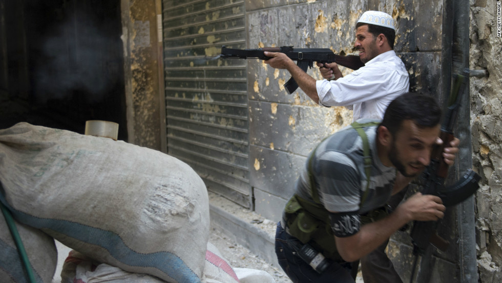 A Syrian rebel fires toward regime forces as his comrade ducks for cover during clashes in Aleppo in northern Syria on Sunday, September 30. Click through the gallery to view images of the fighting in September. <a href='http://www.cnn.com/2012/10/09/world/gallery/syria-unrest-august/index.html' target='_blank'>See photographs of the fighting in August.</a>