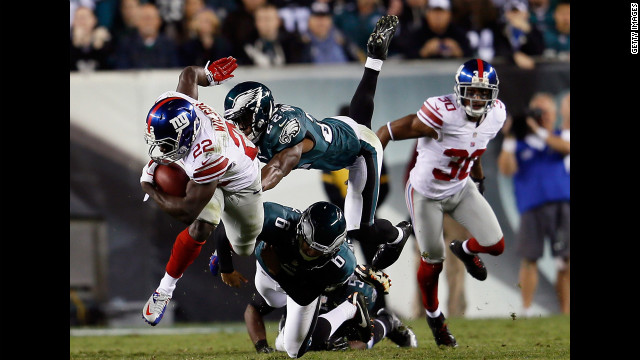 David Wilson of the Giants is tackled by Brandon Boykin, top, center, and Alex Henery of the Eagles on a kick return Sunday.