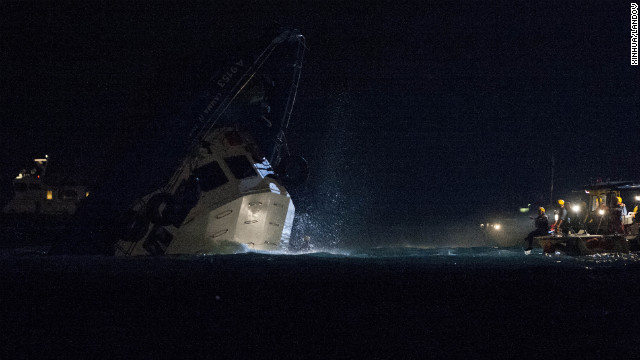 Rescuers approach the sinking vessel late Monday.