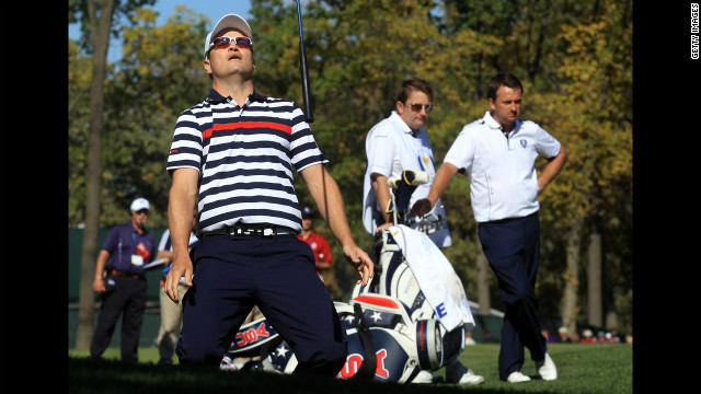 Zach Johnson of the United States reacts to a shot on the ninth hole Sunday as Graeme McDowell, right, and his caddie, Ken Comboy, of Europe look on.