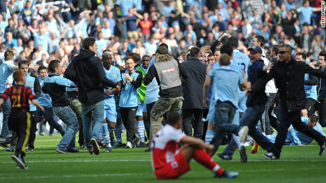 Players and fans of Manchester City celebrate after winning their first English title since 1968. City trailed Queens Park Rangers 2-1 but scored two stoppage time goals to win 3-2 - and so deny city rivals Manchester United the title. The success echoed United's 1999 Champions League triumph in Barcelona, where they beat Bayern Munich 2-1 despite trailing after 90 minutes.