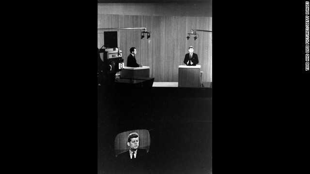 Kennedy and Nixon debate at their lecterns.