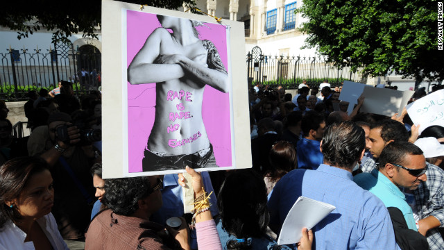 Tunisians hold signs Tuesday while protesting violence against women.