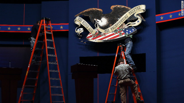 Workers make adjustments to the stage Tuesday ahead of the first presidential debate at the University of Denver.
