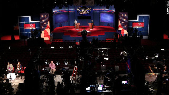 As members of the media prepare their television sets, University of Denver students Zach Gonzales, left, and Dia Mohamed stand in for the nominees during a dress rehearsal for the presidential debate Tuesday, October 2, in Denver. President Obama and Mitt Romney will square off during the first of three debates on Wednesday night.