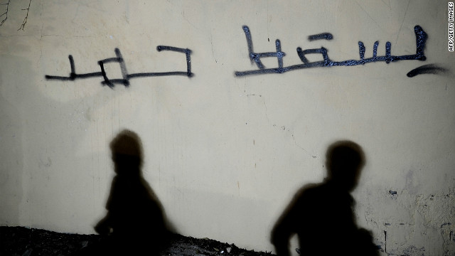 Shadows of Bahraini Shiites are seen on a wall with the Arabic writing 