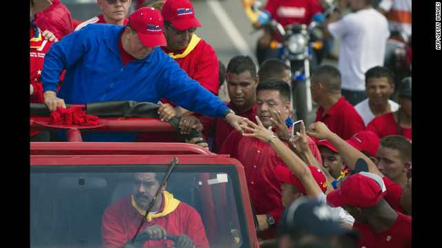 Chavez greets supporters during a campaign rally in Sabaneta on Monday. He dismissed his much younger challenger as a &quot;fly&quot; not worth chasing when challenged to a debate this year.