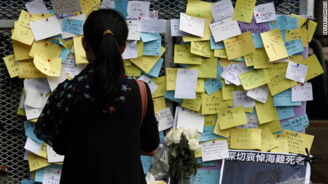 A girl stands in front of a memorial at a ferry pier on Thursday. Hong Kong held a three-day, city-wide mourning period honoring those who died in Monday's ferry collision.