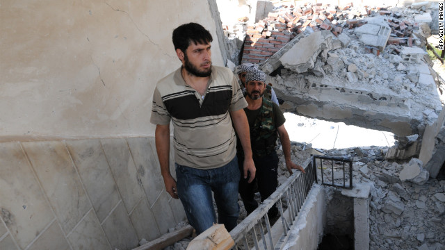 Rebels climb the stairs of a destroyed building Thursday in Tal Abyadh.
