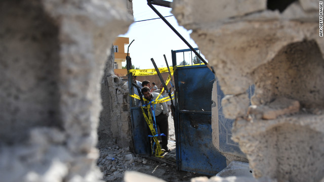 Residents check on a damaged house Thursday, where five Turkish civilians were killed by a mortar in the southern border town of Akcakale on Wednesday, October 3.