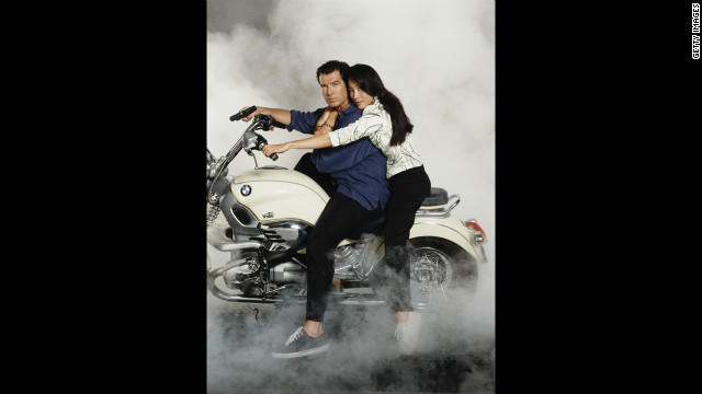 "Pierce Brosnan with Malaysian actress Michelle Yeoh, playng Wai Lin, pose on a motorcylce for ""Tomorrow Never Dies"" in 1997."
