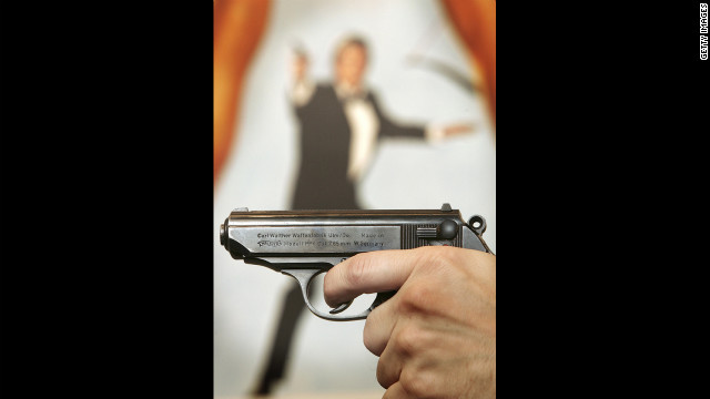 "A Walther PPK handgun is held in front of a poster of the film ""For Your Eyes Only."""