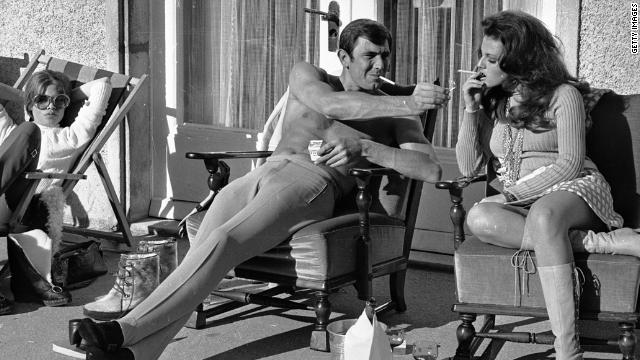 George Lazenby offers co-star Helena Ronee a light during the filming of &quot;'On Her Majesty's Secret Service&quot; in the Swiss Alps in October 1968.