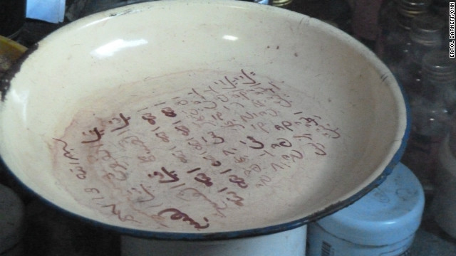 Mama Safi claims to have never studied Arabic yet uses red ink to write the language on a ceremonial plate during a healing procedure.