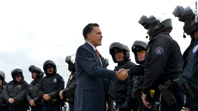Romney greets police officers before boarding his campaign plane in Denver on Thursday.