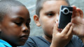 Children living in the favelas of Rio de Janeiro take photo on smartphone as part of a citizen journalism project called Viva Favela