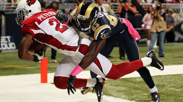 Patrick Peterson of the Arizona Cardinals intercepts a pass intended for Brian Quick of the St. Louis Rams during the game in St. Louis on Thursday, October 4.