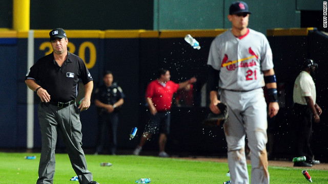 An umpire reacts after bottles and cups are thrown on the field by Atlanta fans angered by the infield fly ruling.